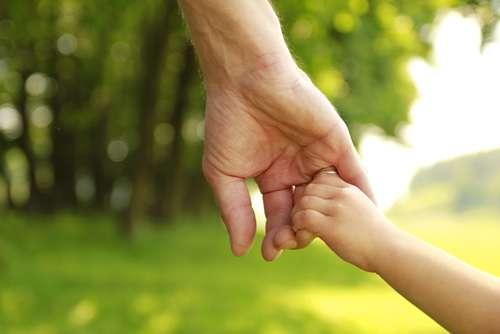 Mann nimmt ein kleines Kind bei seiner Hand