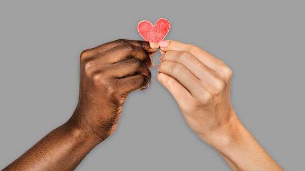 Zwei Hände halten ein Herz aus Papier