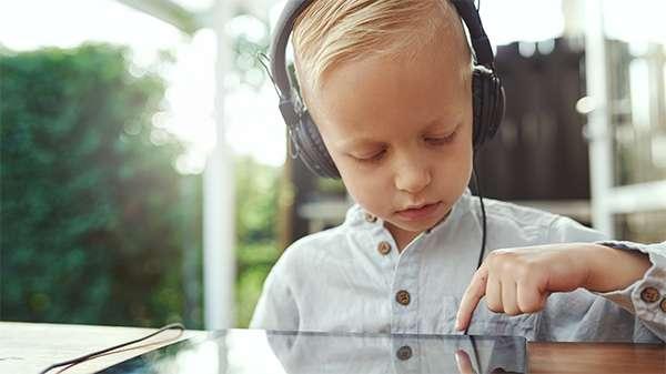 Ein kleiner junge mit Kopfhörern beschäftigt sich mit seinem Tablet