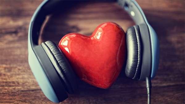 Ein Deko-Herz, dass zwischen den Ohrmuscheln eines Kopfhörers liegt