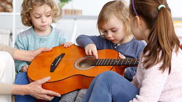 Mehrere Kinder in einem Kindergarten beschäftigen erkunden eine Akkustik-Gitarre